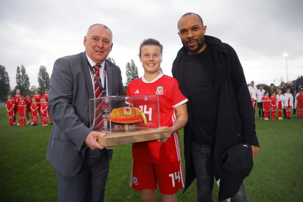 FAW Vice President, Steve Williams (left) and former men's international Danny Gabbidon (right), present Hayley Ladd with her 50th cap.