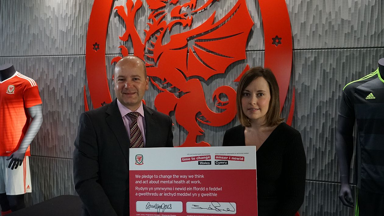 Jonathan Ford signs the pledge and is pictured with Lowri Wyn Jones, Programme Manager of Time to Change Wales.
